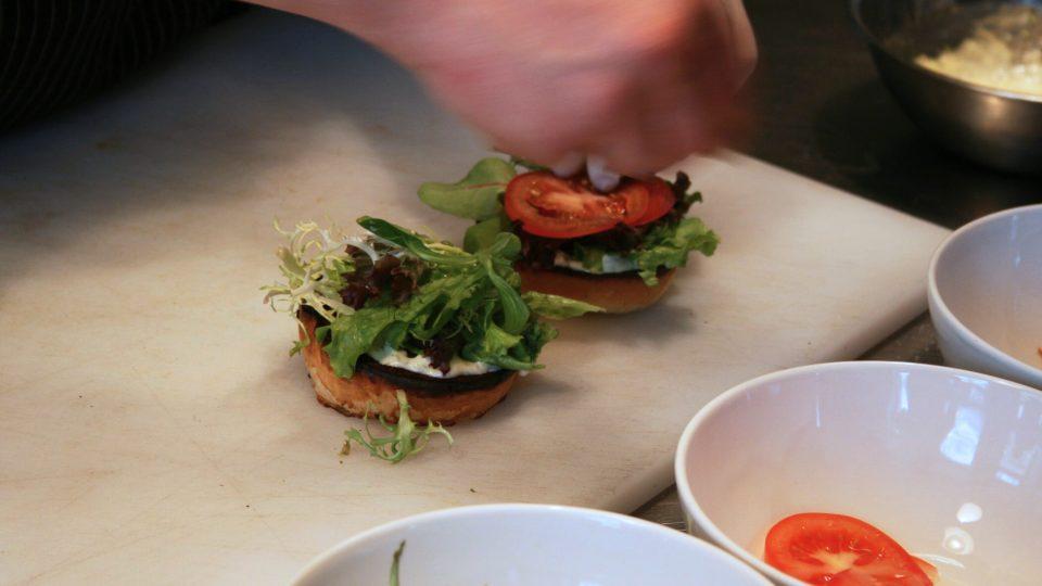 Přidejte listový salát, nakrájené plátky rajčete, maso, opět majonézu a na závěr cibuli