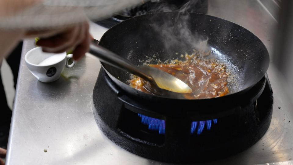 Do rozpálené pánve nalijeme sezamový olej, přidáme nasekaný česnek a zázvor a lehce zpěníme. Přidáme chilli pastu, sójovou omáčku, cukr, kuřecí vývar, rýžový ocet