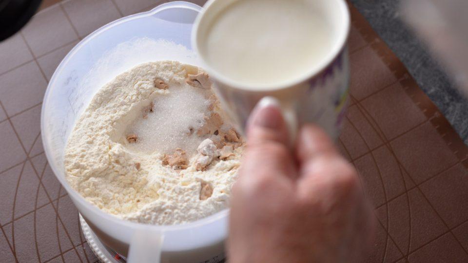 Do mísy prosejeme hladkou mouku a uděláme do ní důlek. Přidáme rozdrobené droždí, cukr a zalijeme mlékem