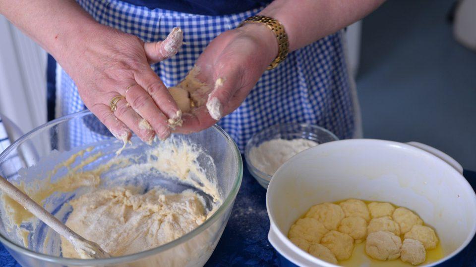 Vytvoříme kuličku, kterou obalíme v mouce a dáme do vymazaného pekáče a hned potřeme rozpuštěným máslem. Vše opakujeme, dokud máme v pekáči místo
