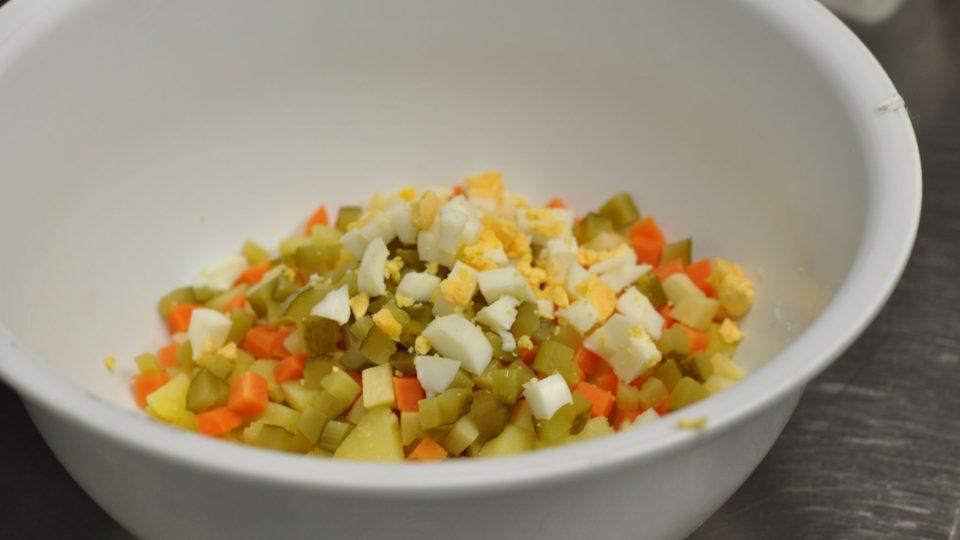 Zeleninu i brambory smícháme v míse, přidáme nakrájená vařená vejce, na kostičky nakrájené nakládané okurky, majonézu i zakysanou smetanu a promícháme