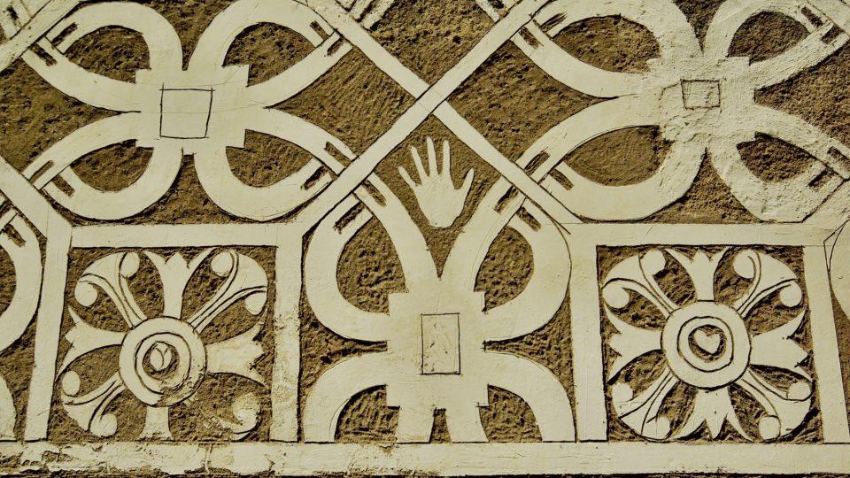 Znamení ruky na sgrafitové fasádě doudlebského zámku připomíná buď jednoho z tvůrců škrábané omítky nebo toho, kdo dílo restauroval