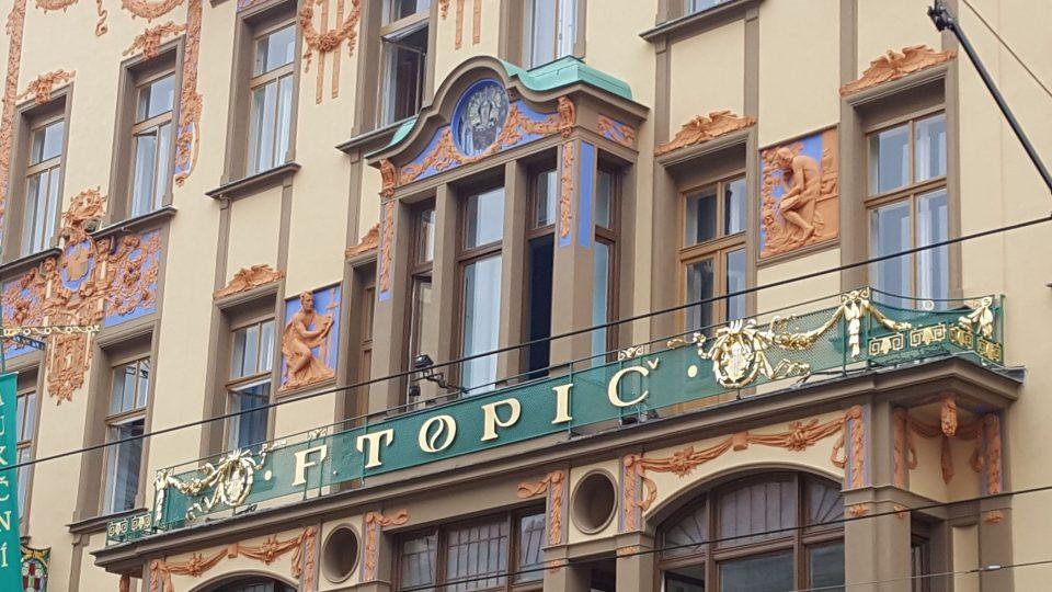 Budova se zdobenou fasádou ve stylu secese, s balkonkem a velkým zlatým nápisem Topič