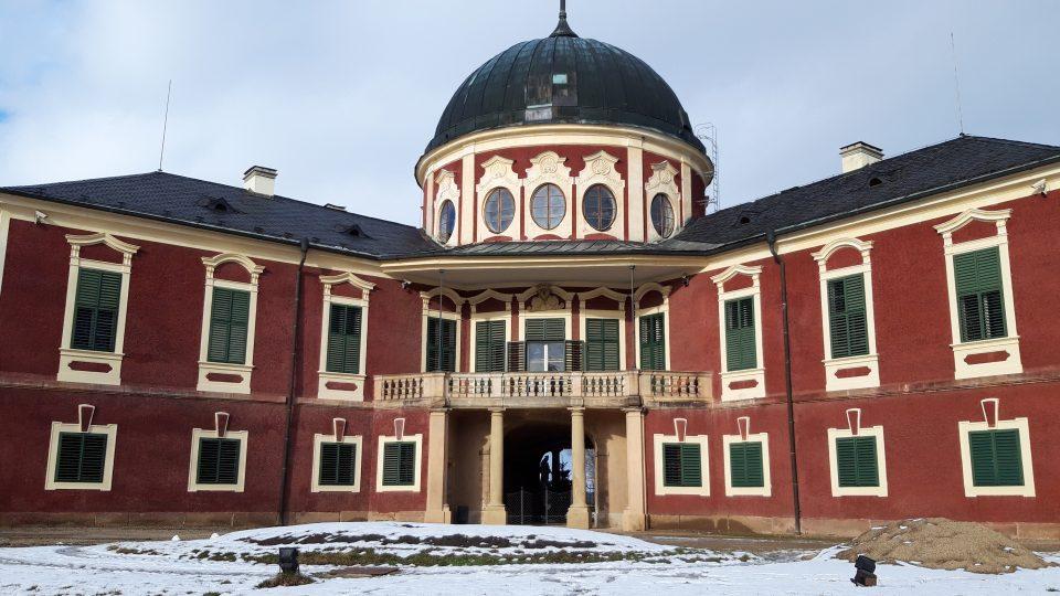 Střední část zámku Veltrusy právě prochází opravou. Za okny můžete zahlédnout žebříky a lešení. Pohled na barokní zámek z parku je ale stále krásný