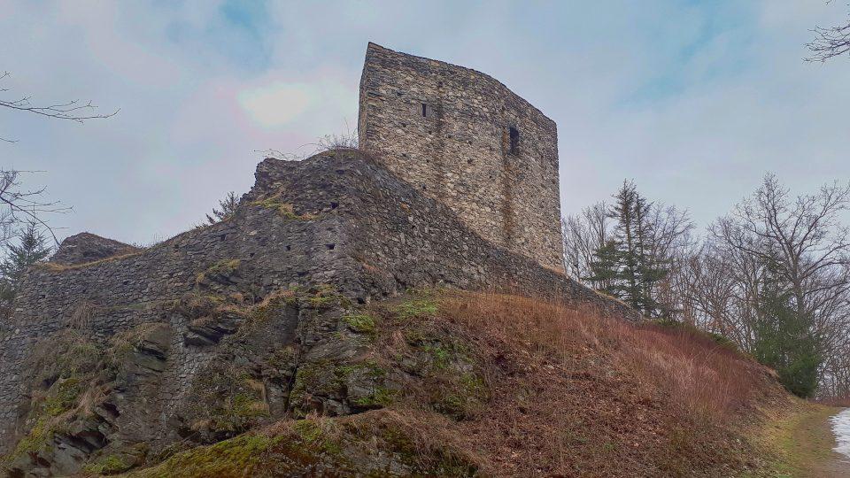 Obranná věž má kolem sebe hradbu, která byla doslova vestavena do skály